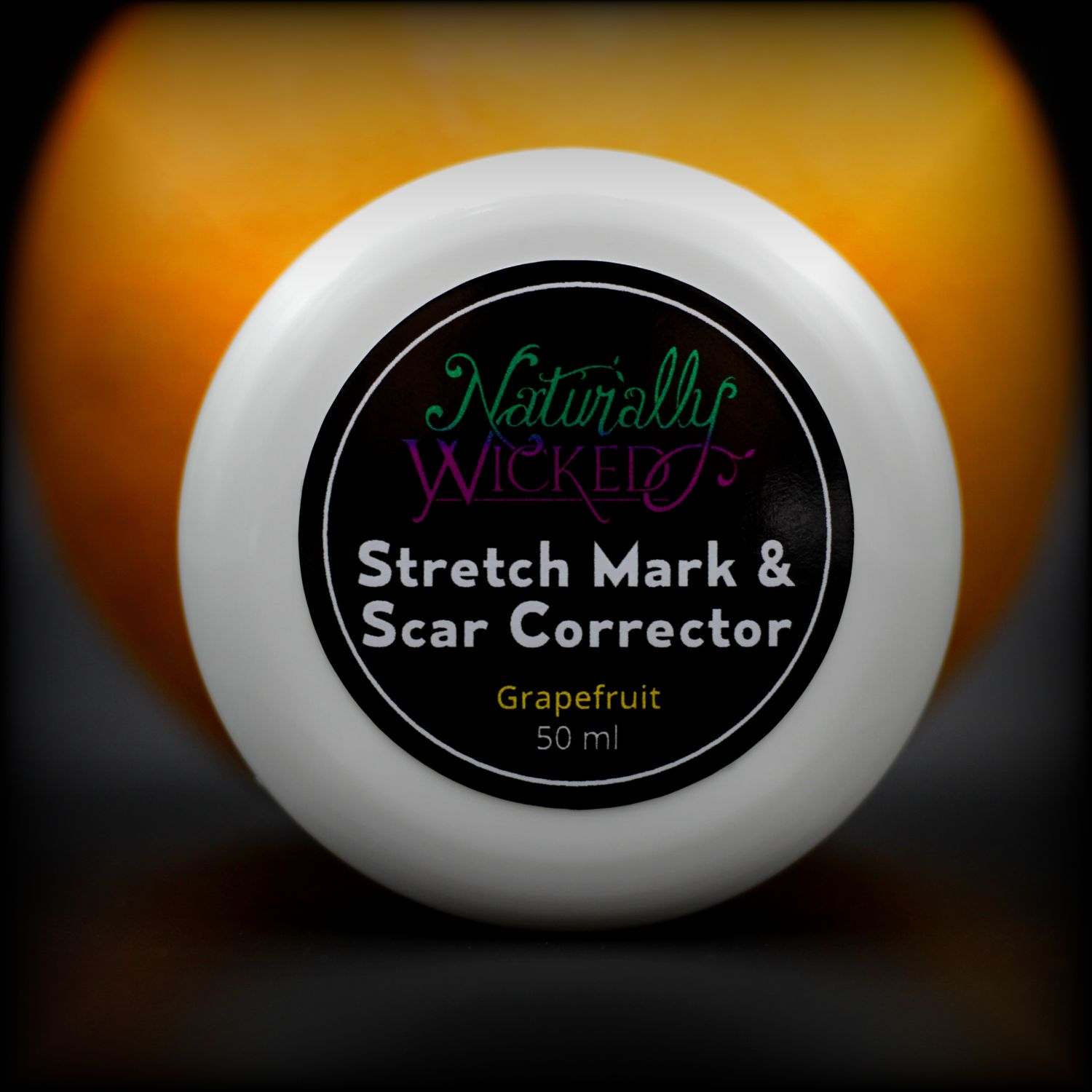 Naturally Wicked Stretch Mark & Scar Corrector Lid In Front Of A Whole Orange Grapefruit