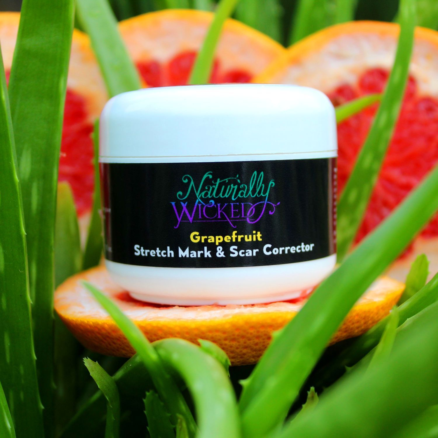 Naturally Wicked Stretch Mark & Scar Corrector Sat In Green Aloe Vera On Top Of Bright Pink Grapefruit With Orange Skin