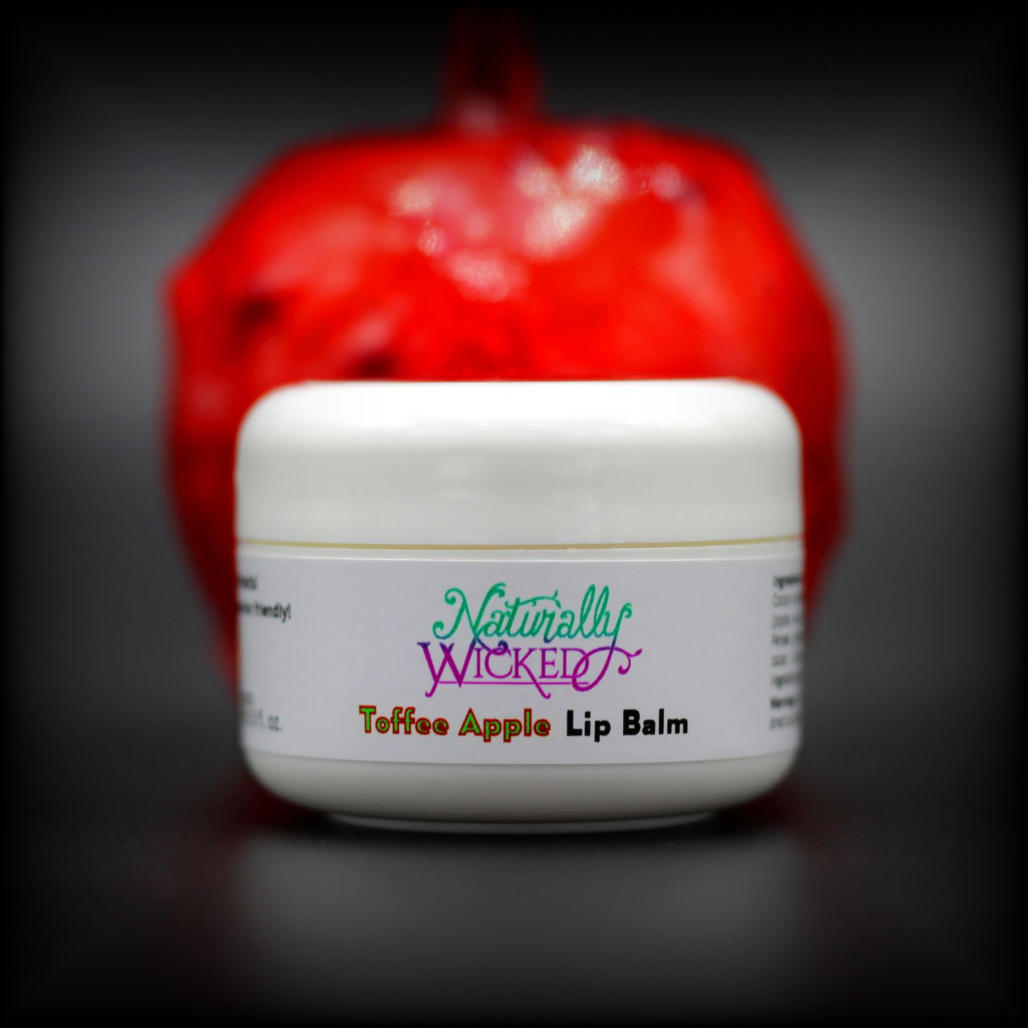 Naturally Wicked Toffee Apple Lip Balm With Bright Red Toffee Apple Behind