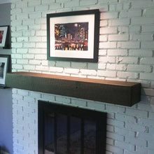 Barnwood box beam mantel with dark stain on white painted brick fireplace