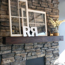 Barnwood box beam mantel with dark stain on stone fireplace