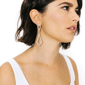 Woman wearing mnimalist kite shaped earrings in sterling silver