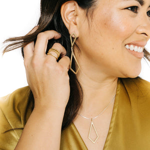 Woman wearing minimalist kite shaped earrings in yellow bronze