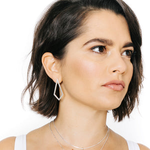 Woman wearing minimalist kite shaped earrings in sterling silver