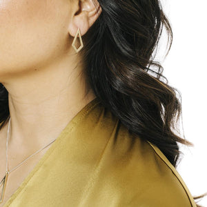 Woman wearing minimalist kite necklace and earrings in yellow bronze