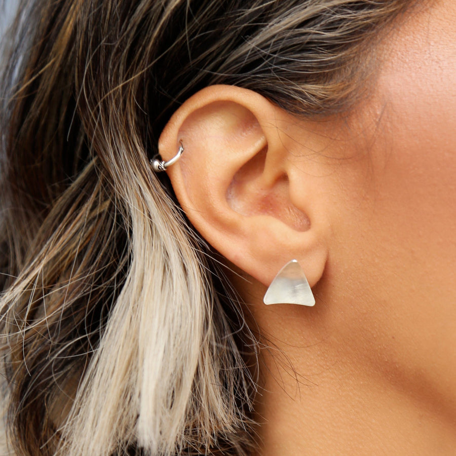 Woman wearing minimalist geometric triangle earrings made with sterling silver