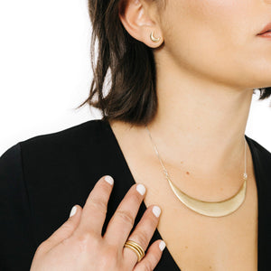 Woman wearing minimalist statement necklace in gold