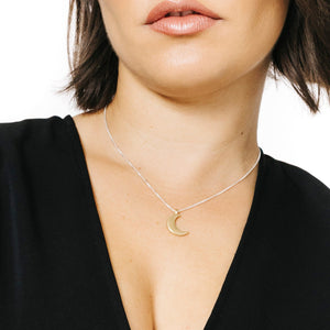 Woman wearing minimalist crescent moon necklace in gold
