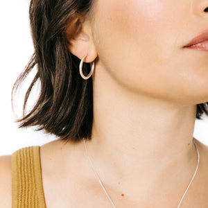 Woman wearing minimalist crescent hoop earrings in silver