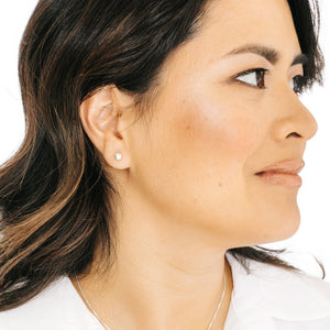 Woman wearing minimalist silver ball earrings