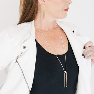 Woman wearing minimalist gold rectangle necklace