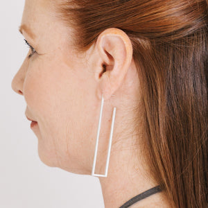 Woman wearing minimalist silver rectangle earrings with open frame