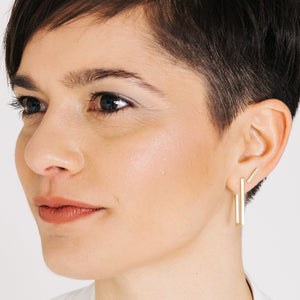 Woman wearing minimalist short gold bar earrings with rectangle hoop earrings