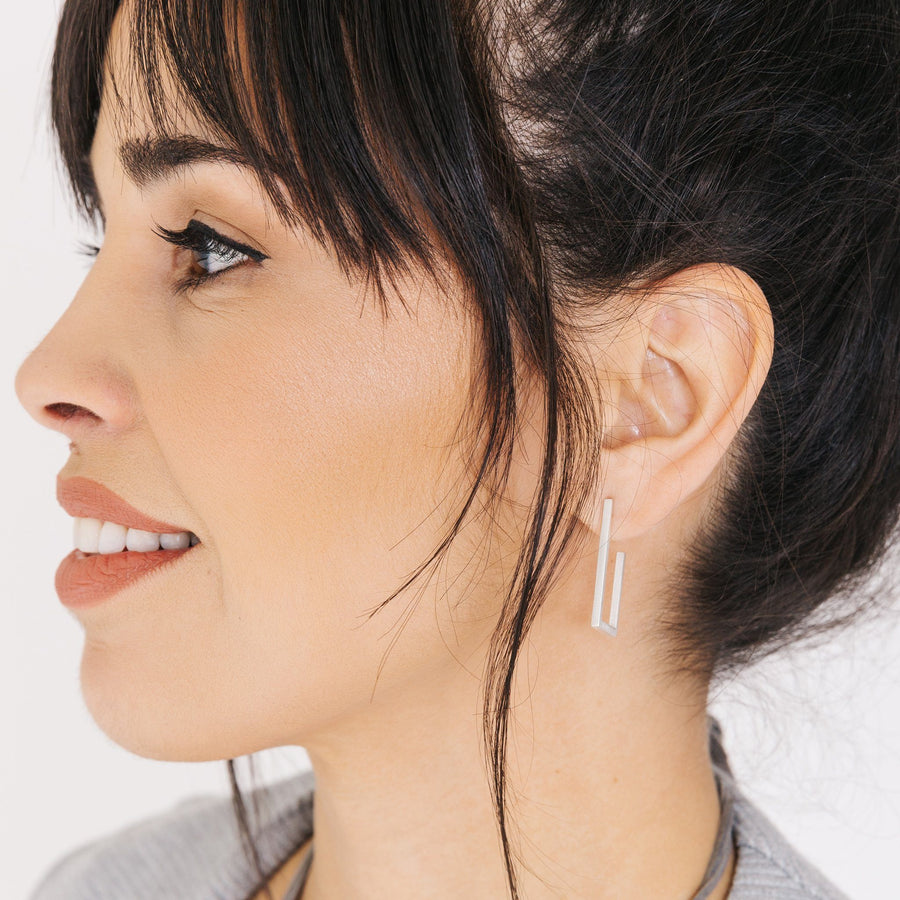 Woman wearing minimalist silver rectangle hoop earrings