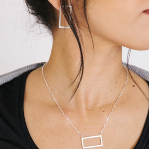 Woman wearing minimalist short frame silver rectangle earrings and rectangle necklace