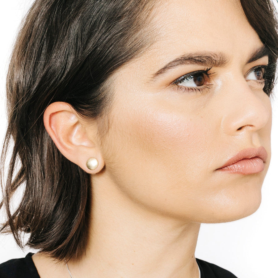 Woman wearing minimalist gold full moon earrings