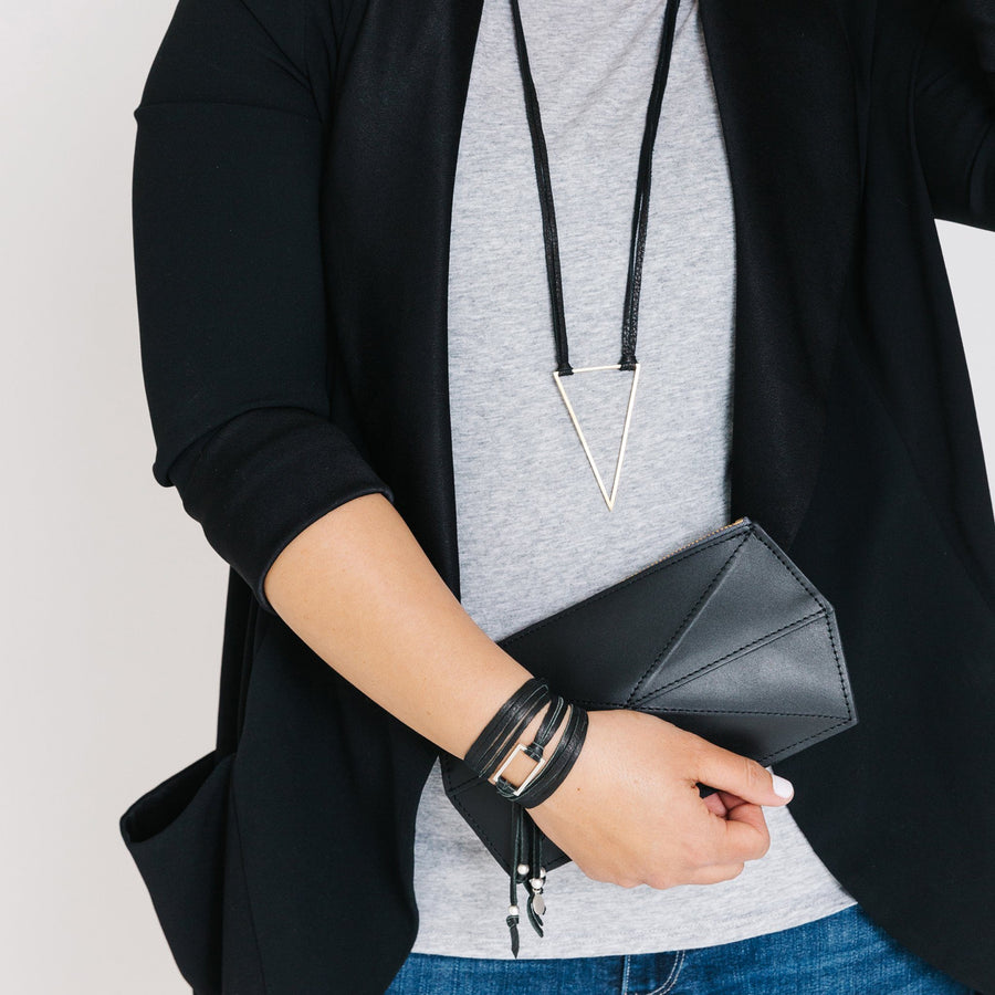 Woman wearing minimalist silver triangle necklace with black leather cord