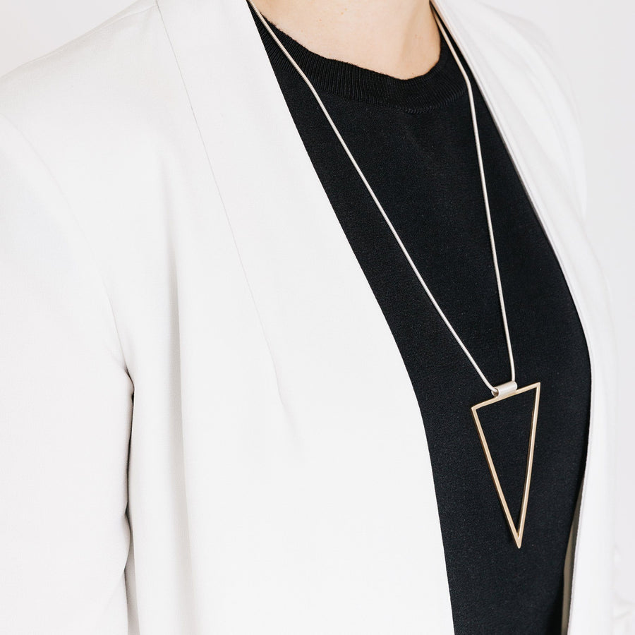 Woman wearing minimalist gold triangle pendant necklace