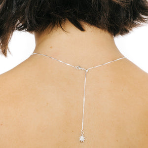 Woman wearing silver necklace chain with small star charm