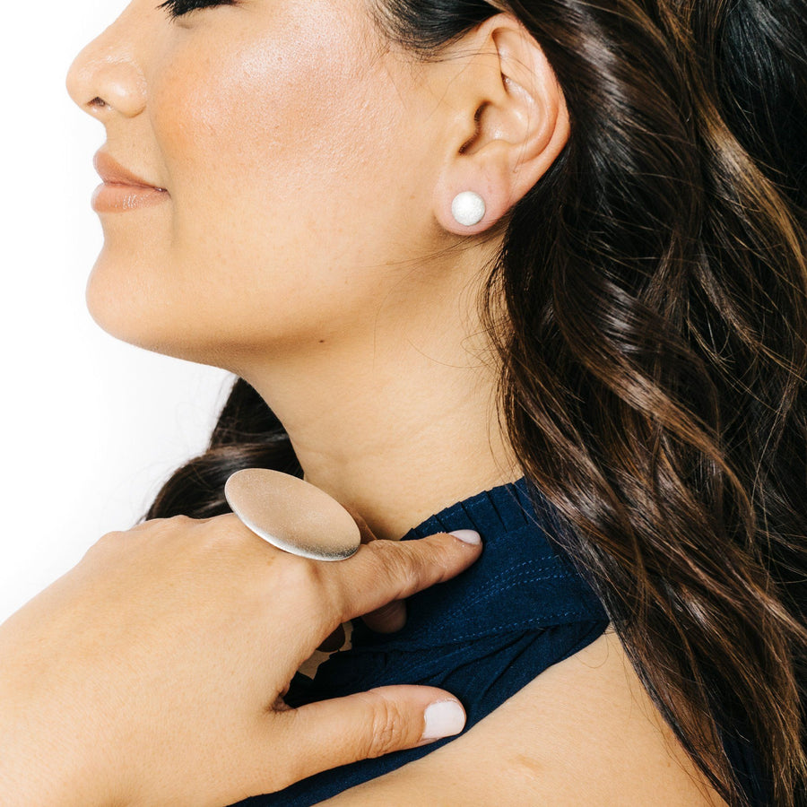 Woman wearing minimalist silver full moon earrings and full moon statement ring
