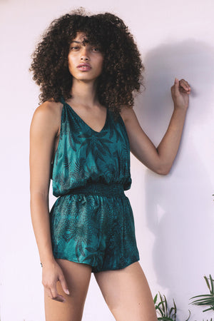 Tie knot back romper in Soul Tree Pring. A deep emerald green background  with black fern silhouette