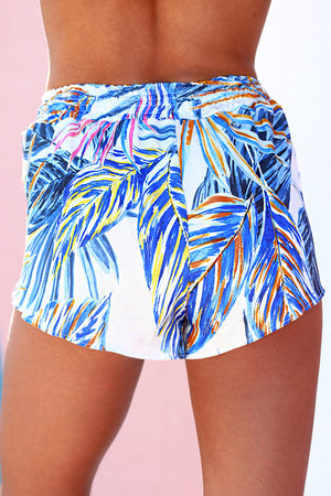 Shorts with tassel tie in Hot Steppa print. Vibrant pallet of multi colored palm leaf print on white background.