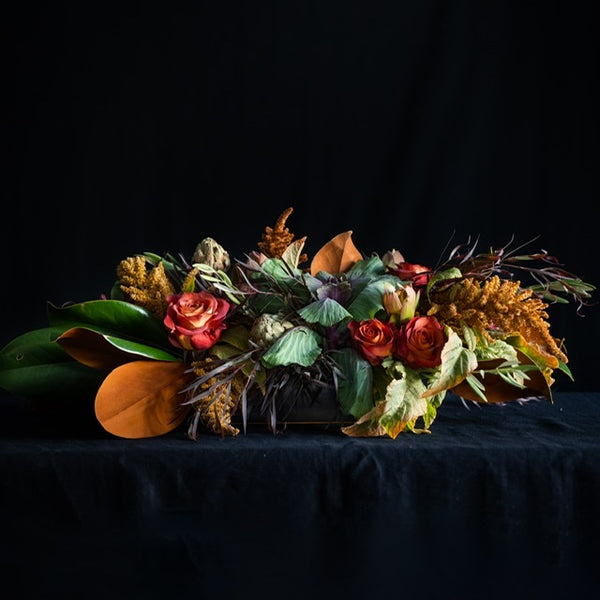 Thanksgiving Punch is a long fall arrangement featuring roses, kale, fall stems, and magnolia leaves. Colors: Reds, Taupes, Brown