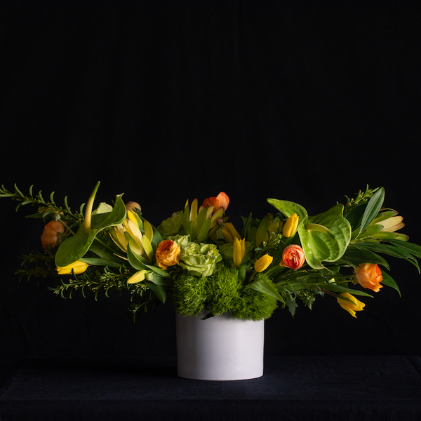 Modern horizontal floral design of green anthurium, green roses, tulips, ranunculus, and premium greenery