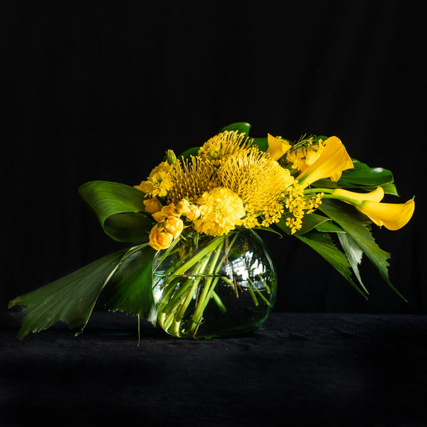 French Pear Martini is a modern design in a glass bowl vessel featuring yellow protea, calla lilies, marigolds, green palms, and monstera leaf. Colors: Yellow