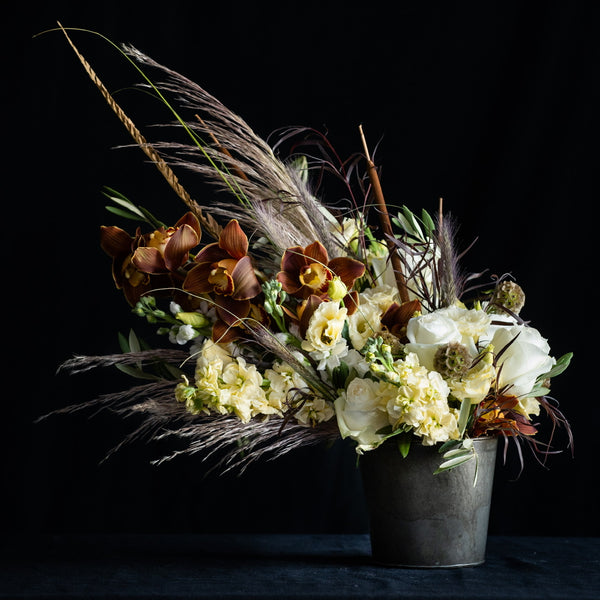 Bourbon Maple Chai Arrangement is in a metal looking vessel and features white roses, pampas grass, cattails, and a beautiful fall orchid. Colors: White, Taupes