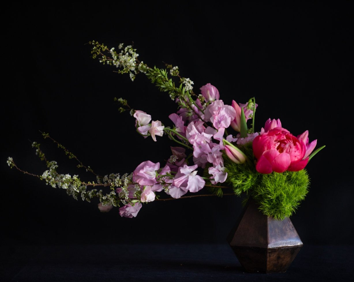 Pink peony, tulips, and sweet peas with blossoming branches in a contemporary design.