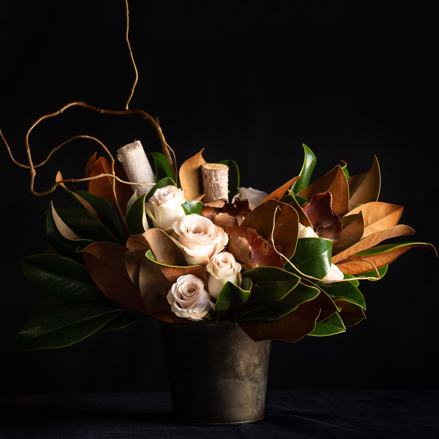 Taupe roses nestled in between magnolia leaves, birch, and curly willow. All around design.