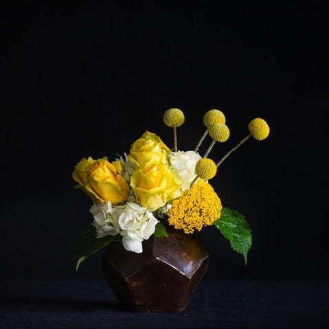 Mother's Day flowers, arrangement of hydrangea, yellow roses and craspedia in a modern container