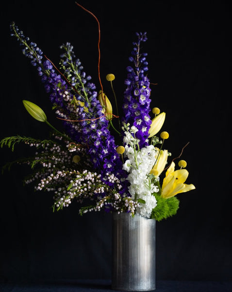 A vertical design of delphinium, lilies, stock, and blooming branches Edit alt text  Edit alt text