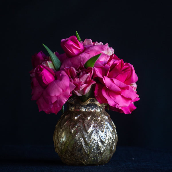 Roses and tulips fill a mercury gold vase. The perfect bedside arrangement