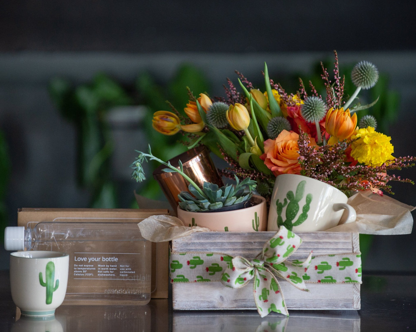 Wooden gift box filled with a planted succulent or cactus, a vim & vigor copper candle, Arizona themed flowers, and your choice of a memo bottle / cactus cup /  or saguaro mug. The box is finished with a cactus bow.