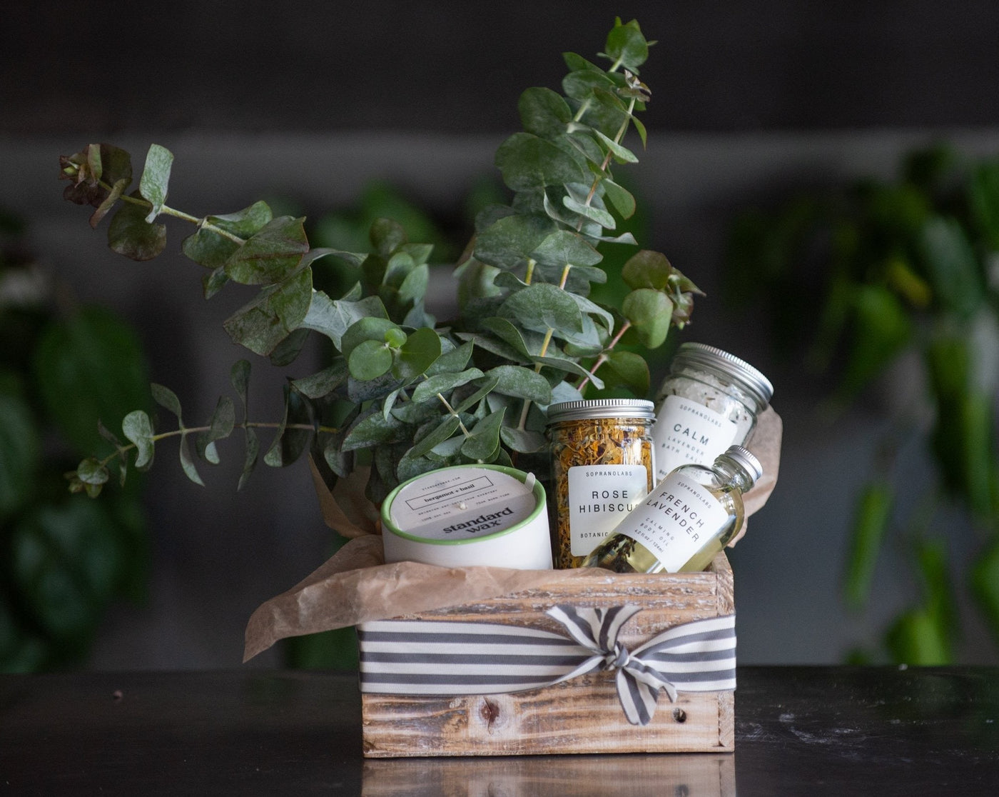 Spa Bounty is a Wooden gift box Filled with body oil, bath salts, botanical steam, standard wax candle, and a bunch of eucalyptus.