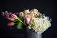 Hydrangea, roses, lilac, tulips and a succulent in a zinc container
