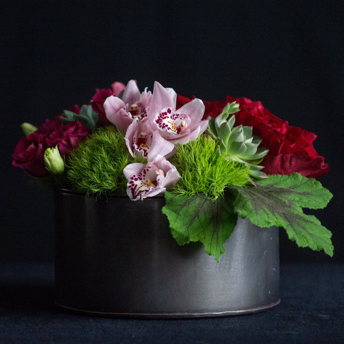 Low, lush design of red and pink flowers with succulents in a black container