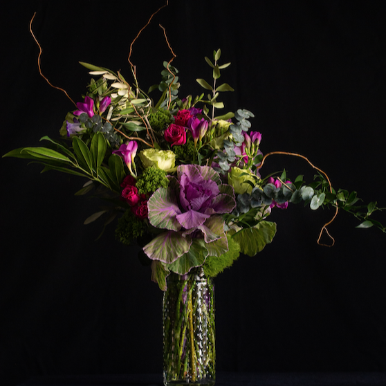 Tall floral arrangement of purple and green - roses, kale, freesia, curly willow in a clear vase