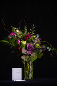 "Tall floral arrangement of purple and green - roses, kale, freesia, curly willow in a clear vase. Pictured with a standard greeting card for scale. Design in 24"" tall."