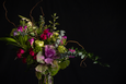 Details of a luxury floral arrangement of purple and green - roses, kale, freesia, curly willow in a clear vase