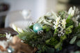 Table design of airplants, succulents, white floral, holiday greens and driftwood with ornaments.