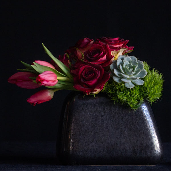 Roses, tulips, and a succulent in a black vase