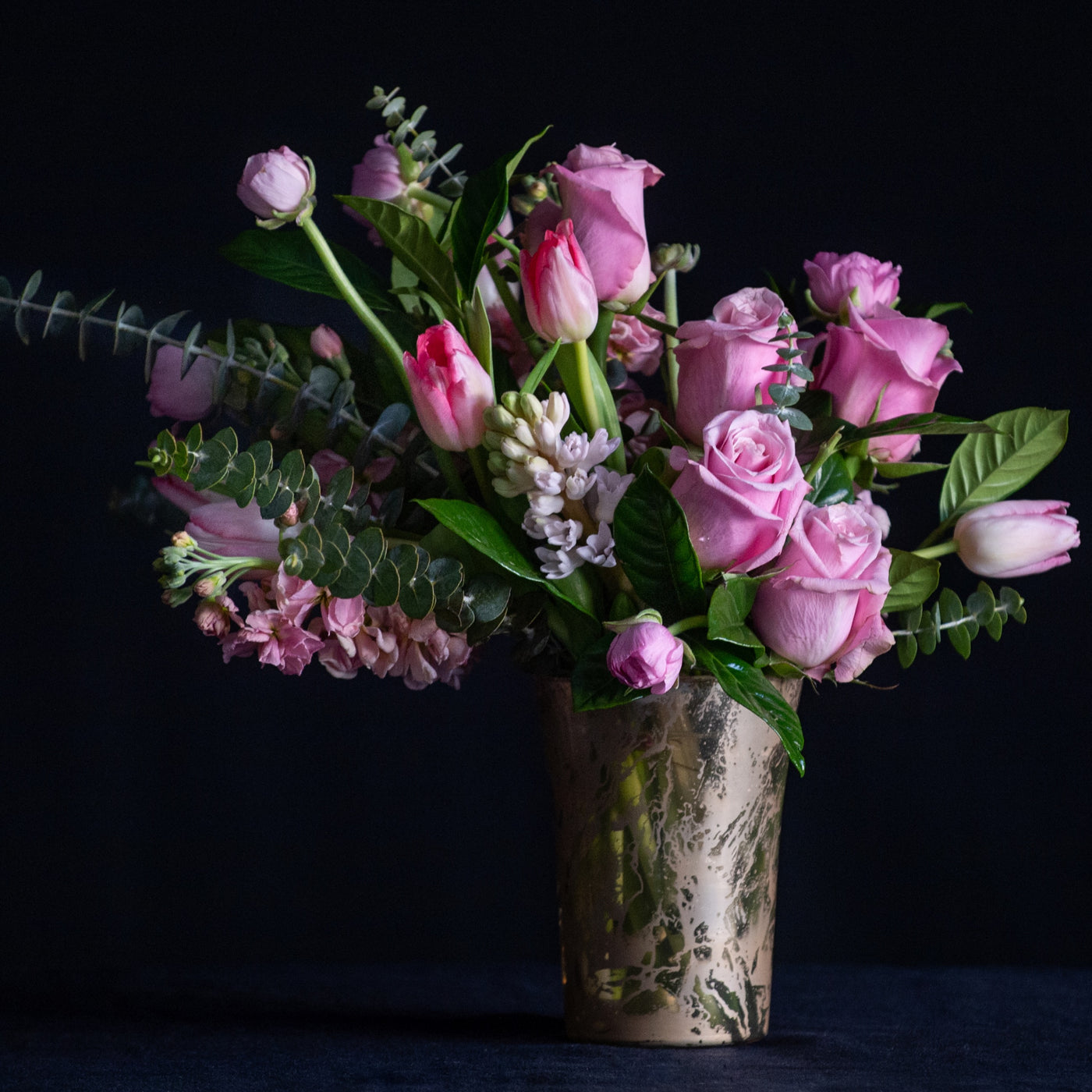 Valentine's Arrangement in a gold mercury vase of pink roses, hyacinth, tulips, and ranunculus