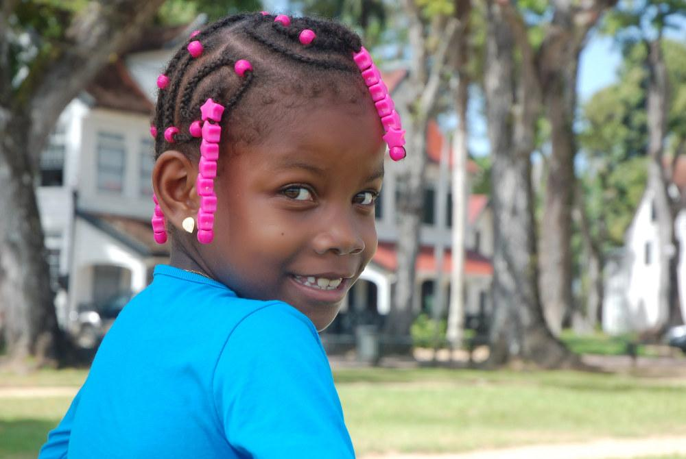 Suriname kid with natural hair in braids and beads