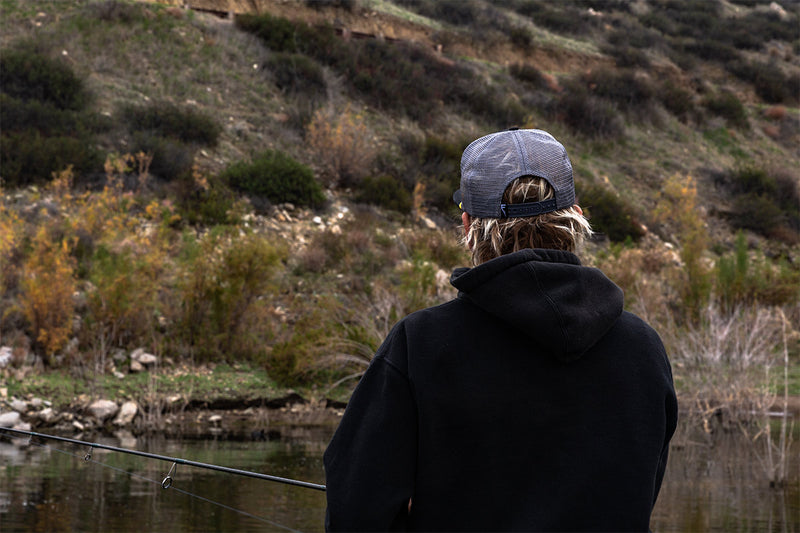 Parker Wright looking at Diamond Valley Lake before casting. Wearing Finatic Tackle trucker badge flatbill hat.