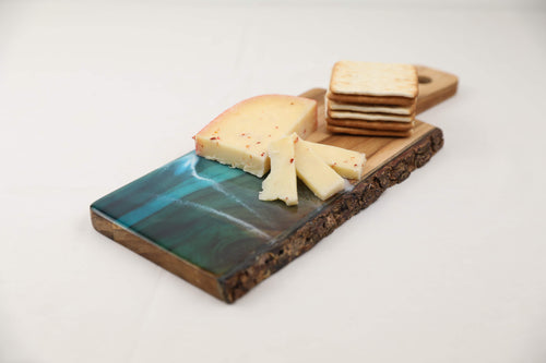 Acacia wood live edge charcuterie board displayed with cheese and crackers. Charcuterie board is made with acrylics and resin and is food safe. Select between a deep ocean colour, a tropical colour, or a teal ocean to bring summer to your home.