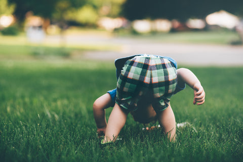 Toddler enjoying the grass bare foot - Photo by Jordan Whitt on Unsplash