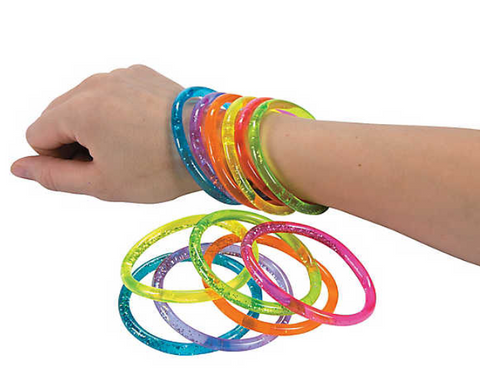 A person holds out their hand with six glittery water bracelets on it, one in each color. Laying in front of their wrist is all six glittery water bracelets on a flat surface.